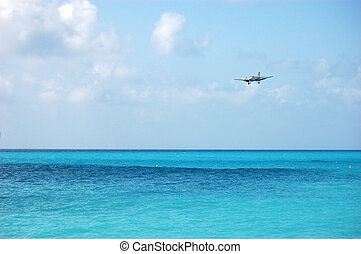 Airplane Landing Over Sea - Airplane flying in low over the...