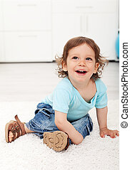 Adorable child laughing on the floor