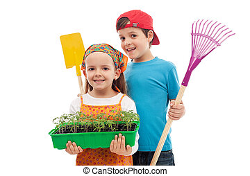 Kids with spring seedlings and gardening tools - isolated