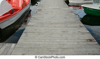 wooden bridge on lake and boats