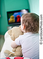 Kid with teddy bear watching TV