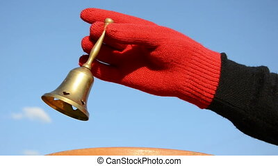 hand with glove and brass bell - hand with red glove and...