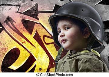 Baby playing war with military helmet against graffiti background with intense orange light