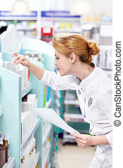 Working - A young pharmacist at the pharmacy
