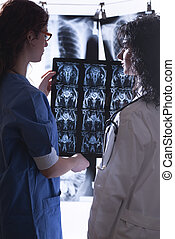 Doctors examine x-rays - Doctors examining different...