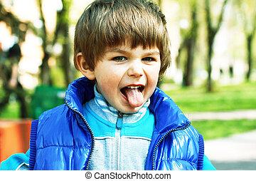 little boy puts out a tongue