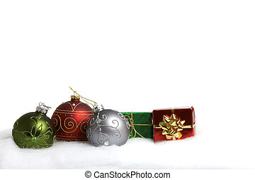 Three Christmas baubles and two small gift packet in the...