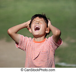 Exasperated young boy - Young boy grabs his head in...