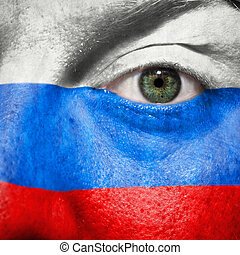 Flag painted on face with green eye to show Russia support