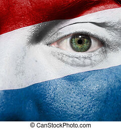 Flag painted on face with green eye to show Luxembourg support in sport matches