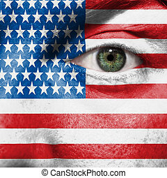 Flag painted on face with green eye to show USA support in...