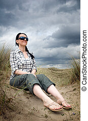 woman sitting in sand dunes