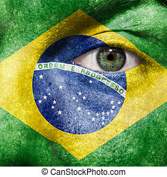 Flag painted on face with green eye to show Brazil support