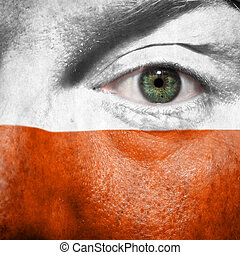 Flag painted on face with green eye to show Poland support