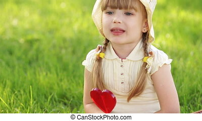 Girl eating lollipop and sitting on - Little girl in the...