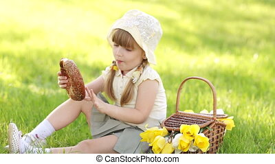 Girl eating bread and sitting in th - Little girl in the...