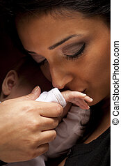 Ethnic Woman Kisses Her Newborn Baby Hand - Young Attractive...