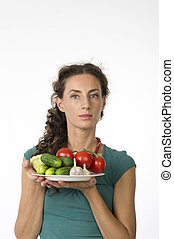 Portrait of a young beautiful woman with vegetables