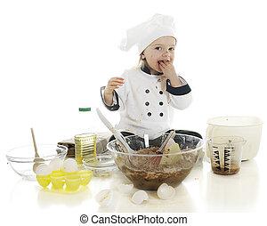 Yum, Yum - An adorable preschool chef tasting a fistful of...