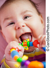 Baby are gnawing a toy - Smiling and playing baby with...