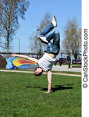 Breakdancer doing a flip on the grass.