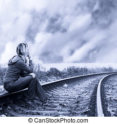 Lonely woman sitting on the rails and thinking.