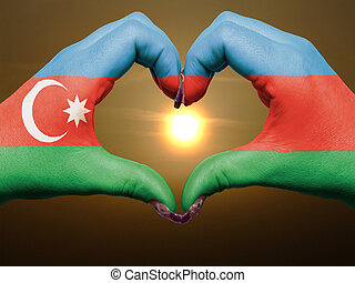 Tourist made gesture  by azerbaijan flag colored hands showing symbol of heart and love during sunrise