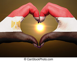 Tourist made gesture  by egypt flag colored hands showing symbol of heart and love during sunrise