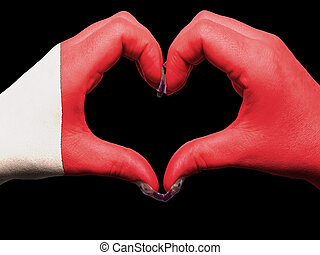 Tourist made gesture  by bahrain flag colored hands showing symbol of heart and love