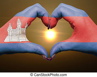 Tourist made gesture  by cambodia flag colored hands showing symbol of heart and love during sunrise