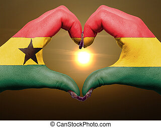 Tourist made gesture  by ghana flag colored hands showing symbol of heart and love during sunrise