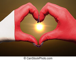 Tourist made gesture  by bahrain flag colored hands showing symbol of heart and love during sunrise