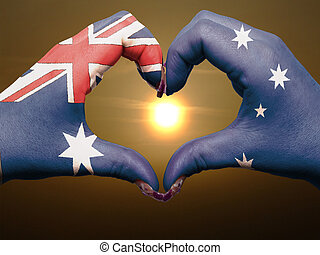 Tourist made gesture  by australia flag colored hands showing symbol of heart and love during sunrise