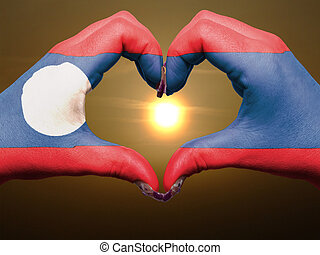 Tourist made gesture  by laos flag colored hands showing symbol of heart and love during sunrise