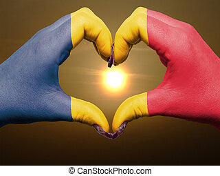 Tourist made gesture  by chad flag colored hands showing symbol of heart and love during sunrise