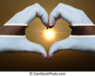 Tourist made gesture  by botswana flag colored hands showing symbol of heart and love during sunrise