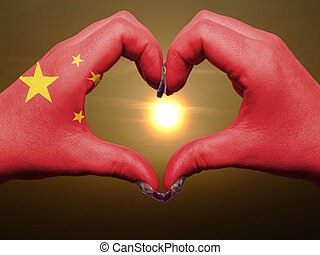 Tourist made gesture  by china flag colored hands showing symbol of heart and love during sunrise