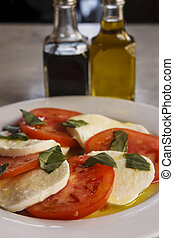 Tomato and Mozzarella Salad garnished with basil with oil...