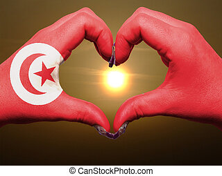Tourist made gesture  by tunisia flag colored hands showing symbol of heart and love during sunrise