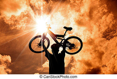 The Silhouette of mountain biker raised bicycle with sunset and cloud background