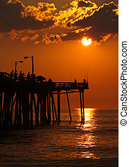 Early-morning anglers are silhouetted against the rising sun on a fishing pier in Nags Head, North Carolina vertical