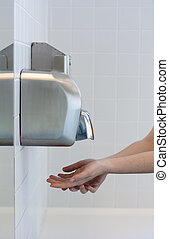 Drying hands in a public restroom (selective focus)