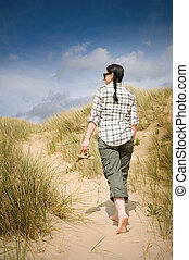 woman walking to beach in sand dunes