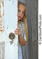 girl peeking around old door - Young girl peeking around old...