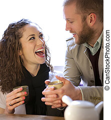 Young couple drinking tea and laughing.