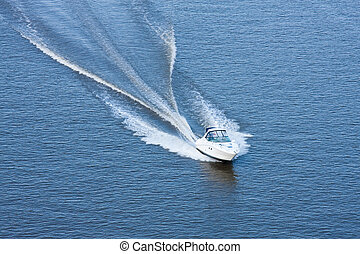 Speedboat going at high speed on blue water.