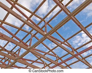 Roof frame construction under cloudy blue sky - Roof frame...