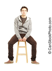 Young man with hip style sitting on stool against white...