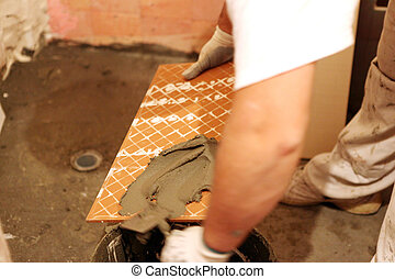 Worker mounting faience on the wall