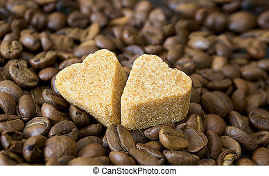 Pieces of sugar on the background of coffee beans.